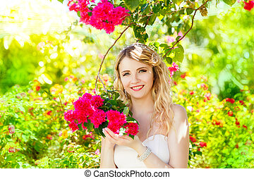 Happy blond bride having fun on a tropical garden. Wedding...