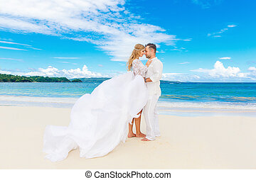 Happy bride and groom having fun on a tropical beach....