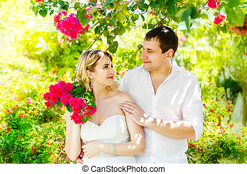 Happy blond bride and groom having fun on a tropical garden....