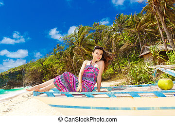 Young beautiful Asian  girl in blue dress on the beach of a tropical island. Summer vacation concept.