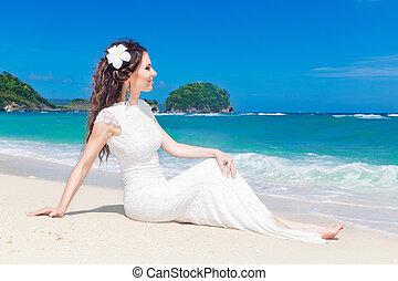 Happy bride having fun on a tropical beach. Wedding and...