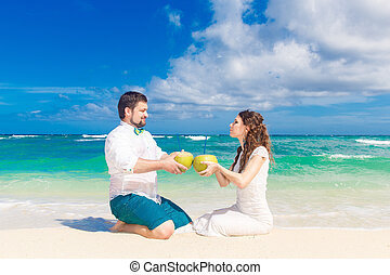 Happy bride and groom having fun on a tropical beach with...