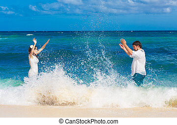 Happy bride and groom having fun in the waves on a tropical...