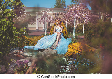 Girl sits on a rock in park. - Girl in a long dress sitting...