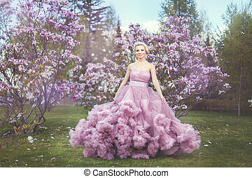Blonde woman among blossoming trees. - Blonde woman among...