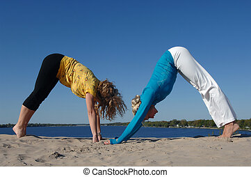 WOMeN PRACTISE YOGA AT THE BEACH - Two beautiful women...