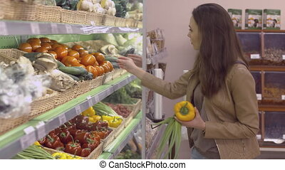 Beautiful girl chooses vegetables at the supermarket, namely...