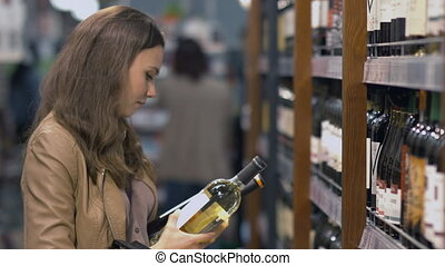 Attractive woman chooses the wine bottle at the supermarket