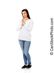 Beautiful young caucasian woman praying.