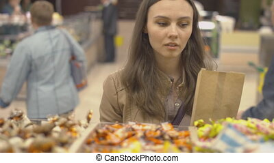 Nice girl chooses sweets at the supermarket and puts them in...
