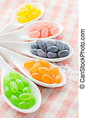 Colorful candies in white spoon.