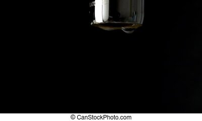 Macro slow motion shot of dripping chrome water tap against...