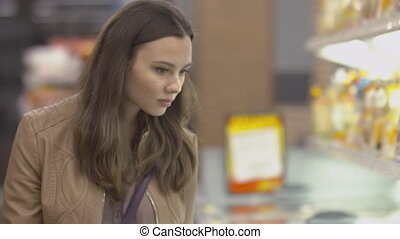 Lovely girl buyer chooses frozen beef in the freezer at the...