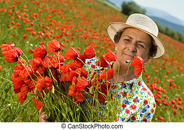 Senior woman on poppy field with a bunch of flowers