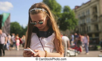 Blond kid girl playing with smartphone sitting on park lawn in city skyline background