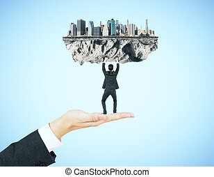 Man upholding city - Businessman miniature standing on hand...