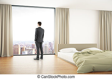 Businessman in bedroom - Thoughtful businessman looking out...
