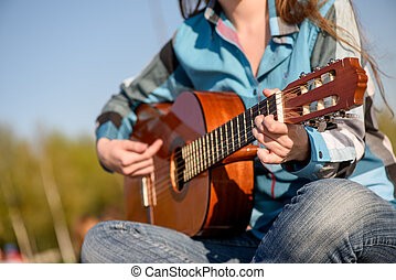 Close up shot without face Woman playng guitar an the coast...