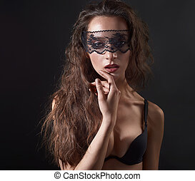Sensual woman posing over dark background with lace mask on...