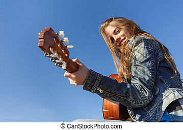 Young woman playing guitar outdoor - Young woman traveller...