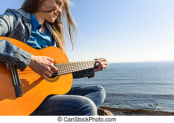 Young woman traveller with guitar outdoor on sea coast -...