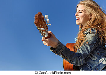 Young woman enjoy playing guitar Blue sky background