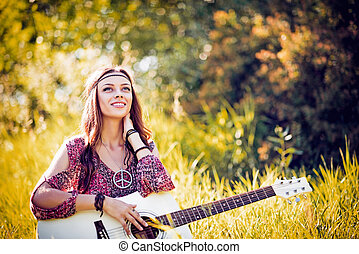 Portrait of beautiful smiling hippie girl with guitar....