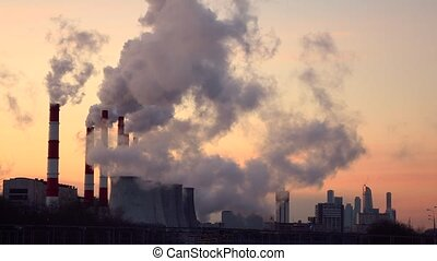 Steaming cooling towers and smoking industrial stacks against gradient sky. 4K
