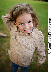 The girl of 7-8 years with a smile looks at camera. - The...