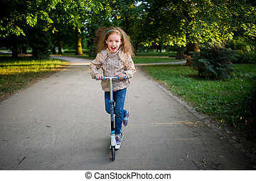 The girl of 7-8 years rides a scooter in city park. - The...