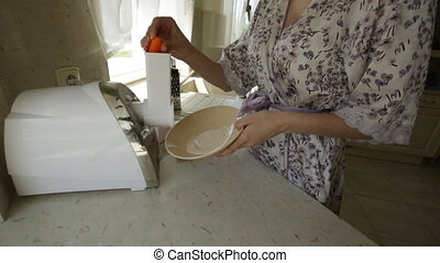 woman cutting carrots in a blender in the kitchen