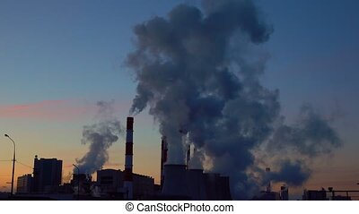 Steaming and smoking factory stacks against late sunset sky....