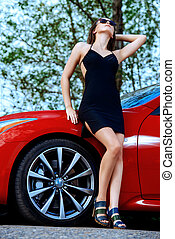 pleasure - Attractive young woman near the red sports car....