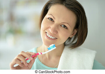 Woman brushing her teeth - Woman standing in bathroom and...