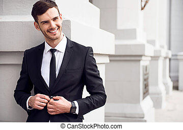 Cheerful man leaning on the wall - Positive worker Pleasant...
