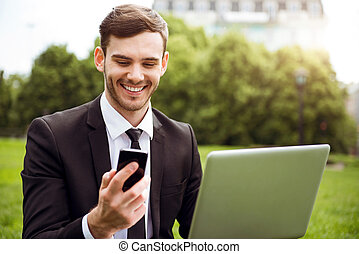 Handsome delighted man sitting on the grass - Share...