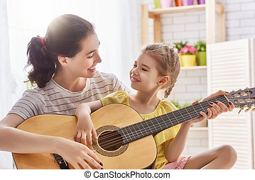 Mother and daughter playing guitar