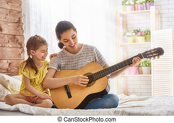 Mother and daughter playing guitar - Happy family. Mother...