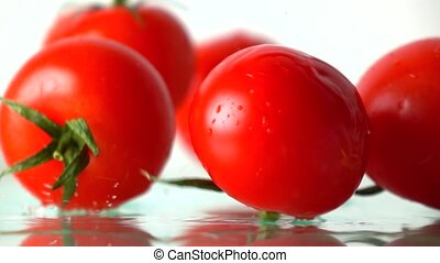 Red ripe tomatoes hit wet glass surface with splashes and...