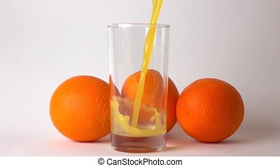Three whole oranges and orange juice being poured into glass. Super slow motion