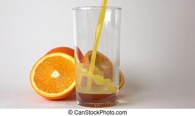 Cut and whole orange and orange juice being poured into glass. Super slow motion