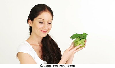Young attractive woman playing with and offering green grape...