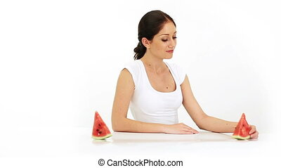 Young attractive woman eating water melon fruit on white
