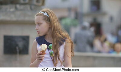 Little girl eating Ice Cream on a Hot Summer Day at Playground in Park, Children