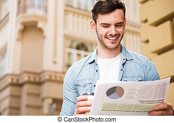 Handsome cheerful man reading newspaper - Involved in news...