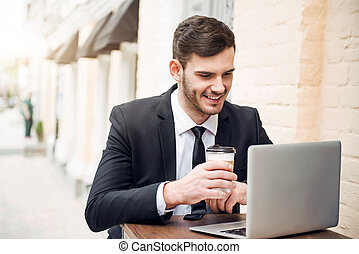 Handsome cheerful man using laptop - Busy days Pleasant...