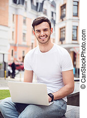 Pleasant delighted man using laptop - Express gladness...