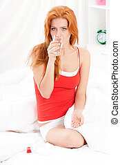 Woman in bed taking pills - Beautiful caucasain woman in bed...