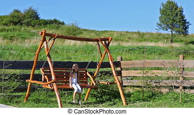 Little girl swaying on wooden chain swing in rural playground