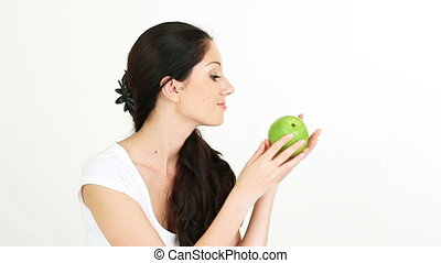 Young attractive woman playing with and offering green apple...